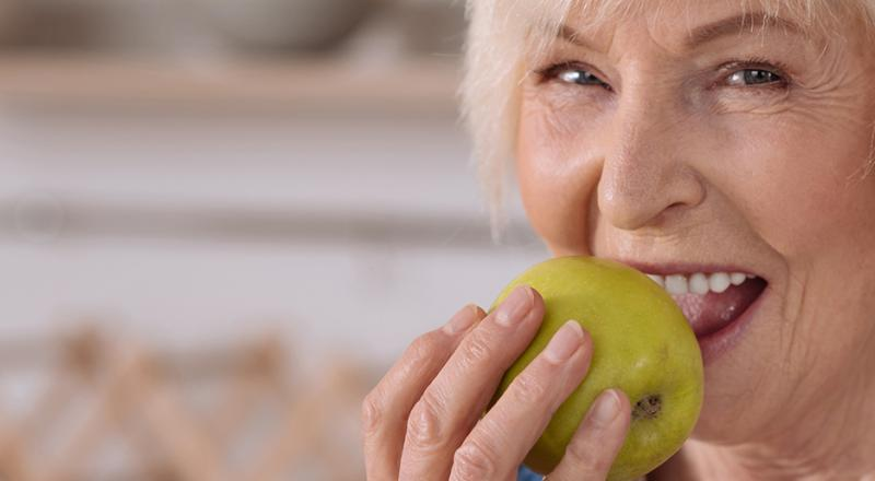 old woman eating apple